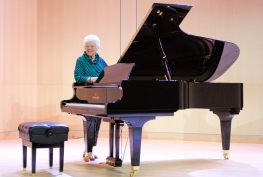 Lila Stewart and the Shigeru Kawai piano that she has given to the Longmont Museum's Stewart Auditotrium